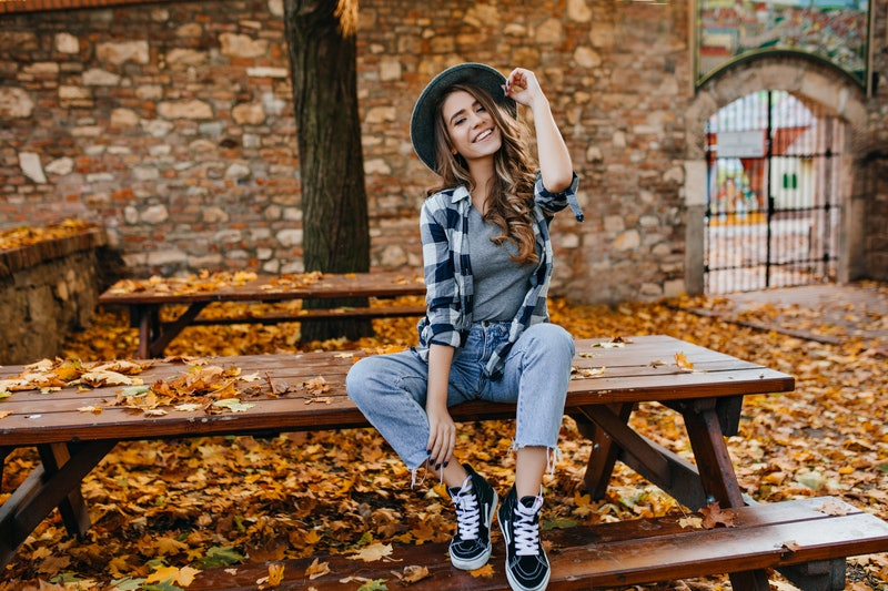 Carefree young woman in trendy vintage pants sitting on table in park and laughing. Curly cute girl in good mood posing in autumn day, enjoying good weather.