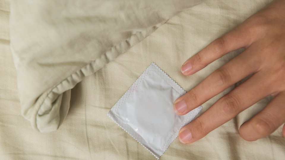 Woman's hand in bed touch a condom