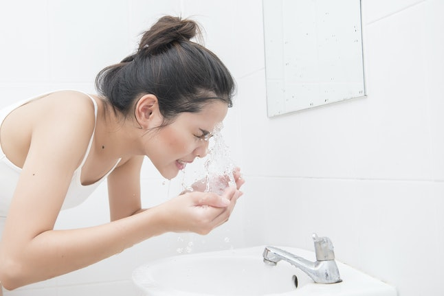 Beautiful asian woman is washing her face