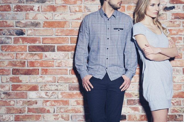 Angry young woman standing next to her boyfriend