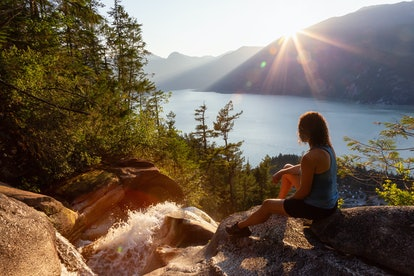 Adventurous Girl is sitting on top of a Beautiful Waterfall, Shannon Falls, and watching the sunset....