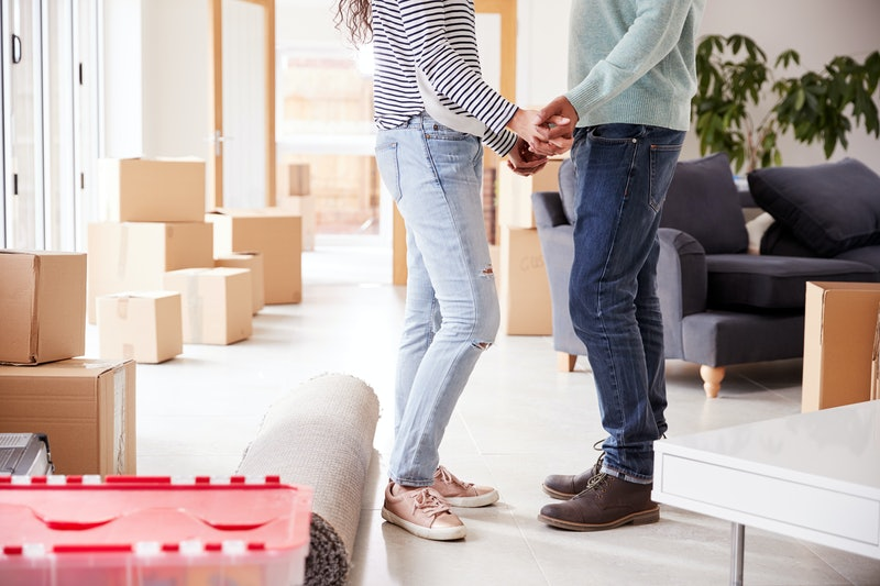 Close Up Of Loving Couple Holding Hands Surrounded By Boxes In New Home On Moving Day