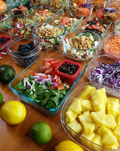 Vegan vegetarian meal prep on wooden table with colorful fruits and vegetables, weekly meal prep spr...