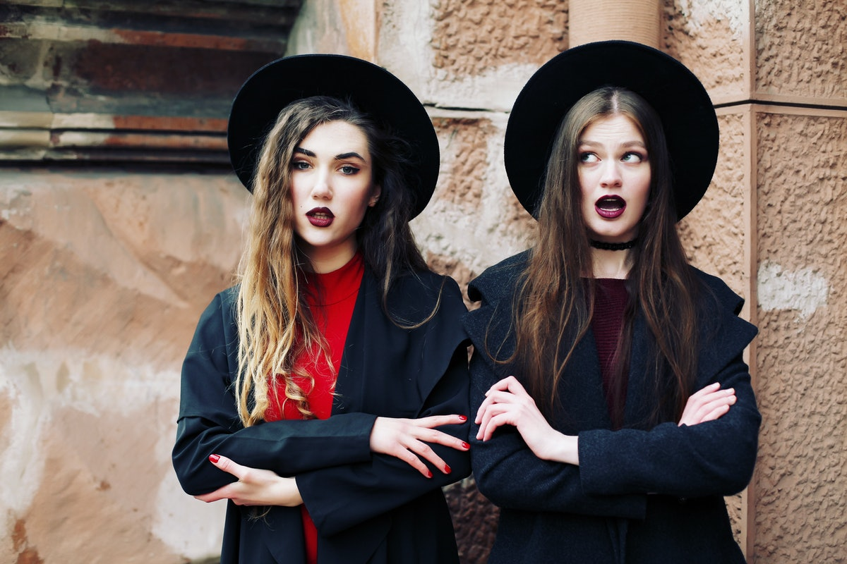 Surprise face, emotions, two best friends wearing stylish outfit, black hat, sunglasses, dress. Bloggers. Curly hairstyle and fashionable makeup. Bright purple lips.