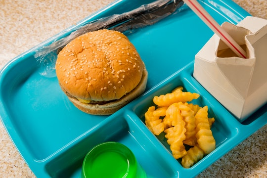 Elementary school lunch cheeseburger with ripple cut french fries gelatin and milk on blue tray