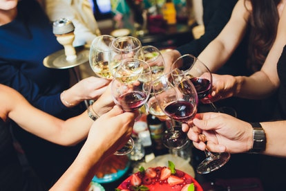 Cropped close up photo of glasses with champagne. Young people are toasting to celebrate the event. Table is full of tasty food and drinks.