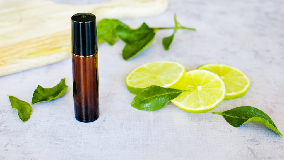 Essential oil roller bottle with lime slices, lime leaves on a concrete bench