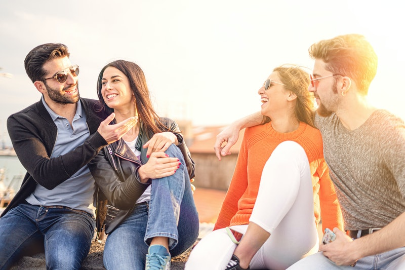 Two couples of friends talking and relaxing together sitting in a small wall during the sunset - mid season lifestyle concept
