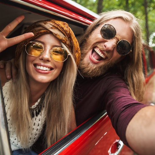 Photo of european hippie couple smiling and showing peace sign while driving retro minivan in forest