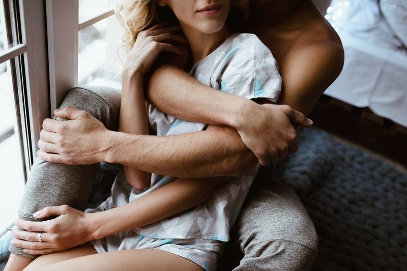 Stylish interior. A couple near the window, under one blue blanket of large mating. Gentle embrace and kisses. Blonde. Floor lamp. Athletic build. Gray pajamas in hearts. Love story.