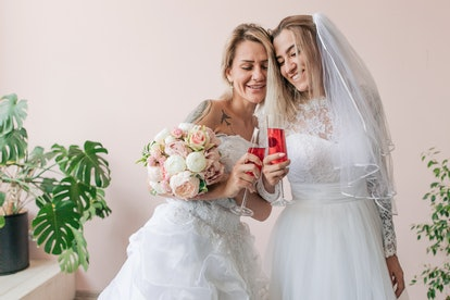 Lesbian in wedding dresses holding bouquet of flowers with champagne standing on pink wall background