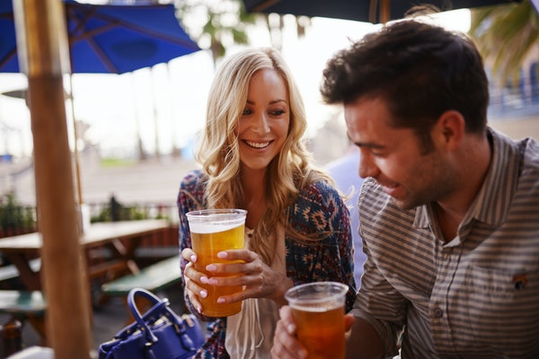 romantic couple drinking beer at outdoor restaurant