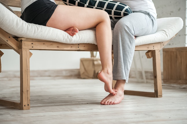 Male and female legs at home close up and copy space. Woman flirting with a man's legs