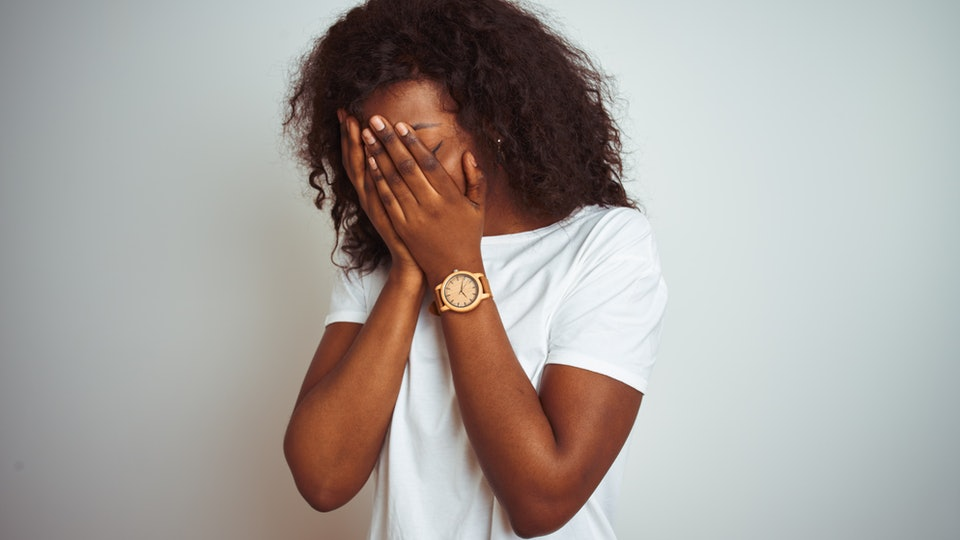 Young african american woman wearing t-shirt standing over isolated white background with sad expression covering face with hands while crying. Depression concept.