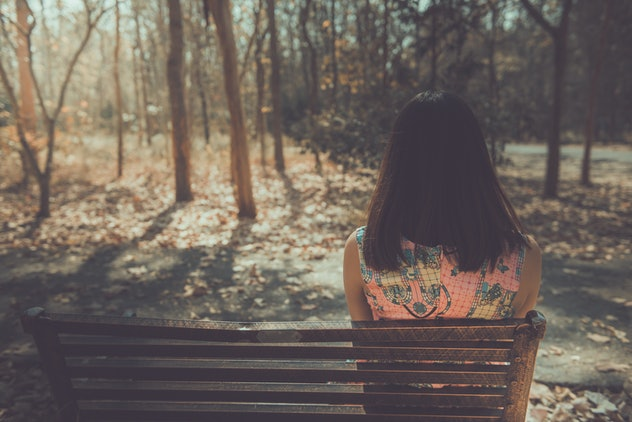 Sad woman sitting on the bench from back angle in the park vintage style,She passed the story lot wo...