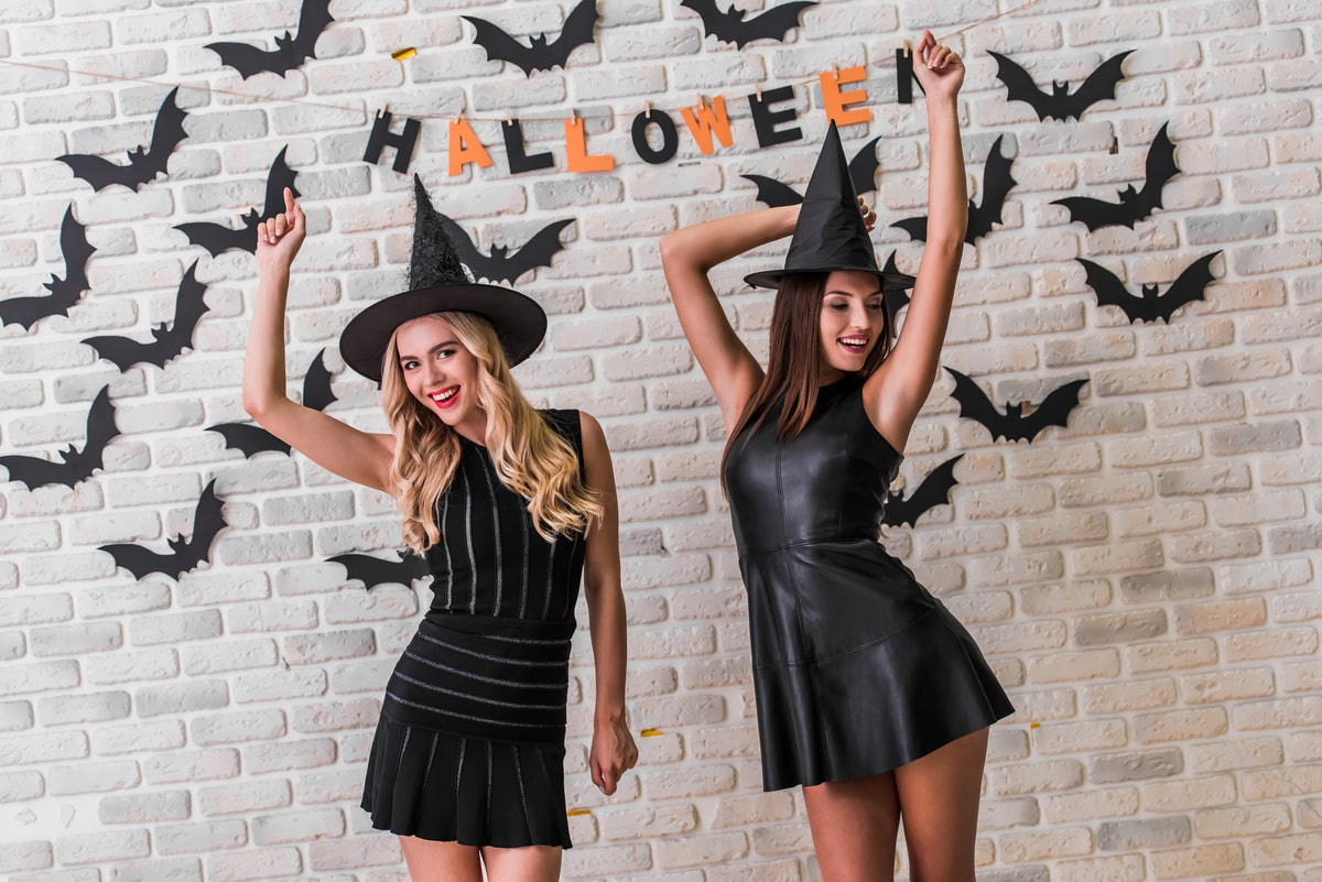 Beautiful girls in black dresses and witch hats are dancing and smiling, on background decorated for Halloween