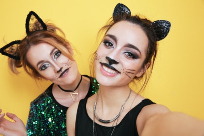 Beautiful young women with cat makeup and ears as their Halloween eye makeup
