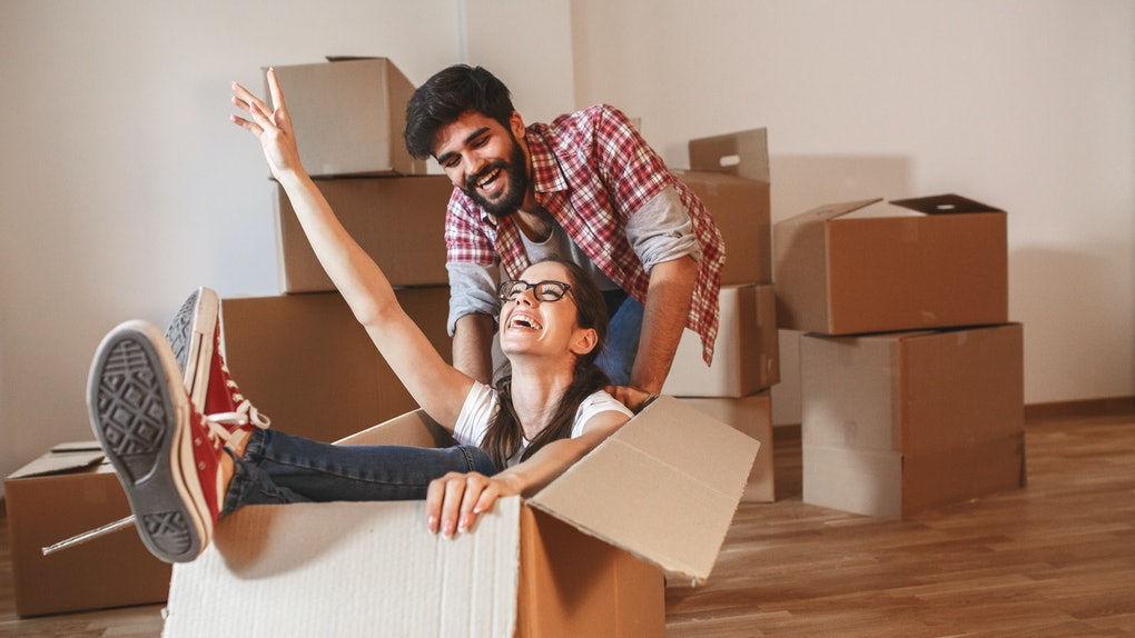 Young couple moving into a new home.Woman sitting in cardboard box while man pushes her all over the room.Real estate funny concept.