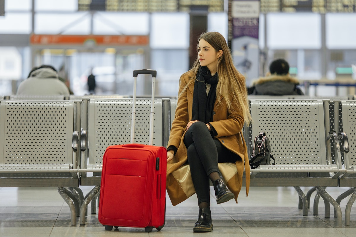 A woman in a long brown winter coat and boots with a red suitcase sits at the airport.