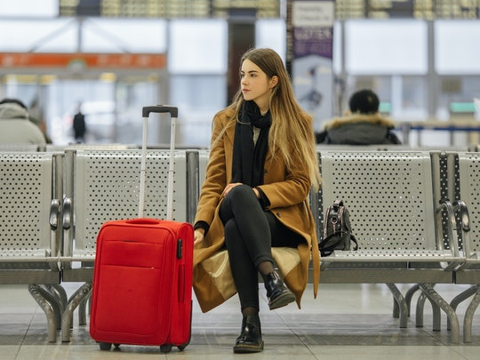 Airport woman waiting in terminal. Air travel concept with young casual business woman sitting with carry-on hand red bag.