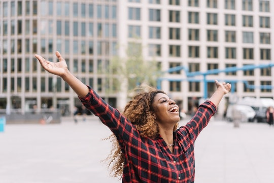 Joyful young African woman laughing and celebrating with open arms in an urban street with copy spac...
