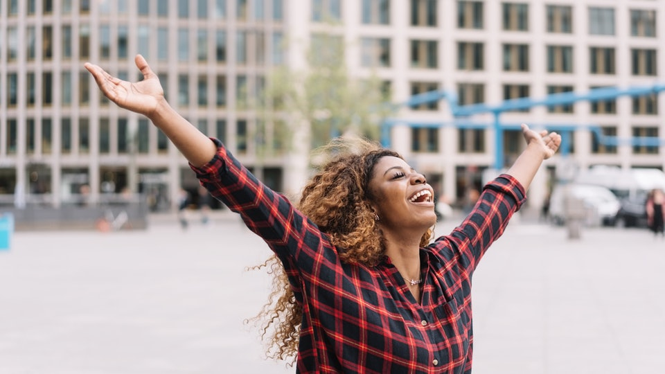 Joyful young African woman laughing and celebrating with open arms in an urban street with copy space