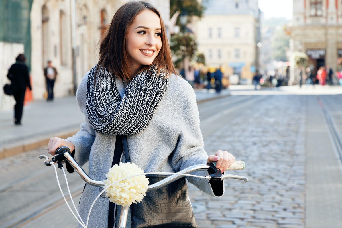 Lovely young woman, wearing in gray jacket and scarf, with black bag, posing with bike on the street of old European city, on sunny day, waist up
