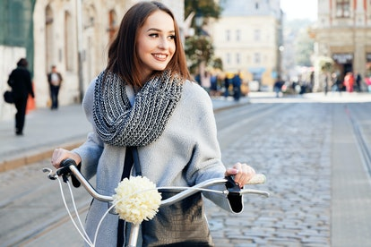 Lovely young woman, wearing in gray jacket and scarf, with black bag, posing with bike on the street...