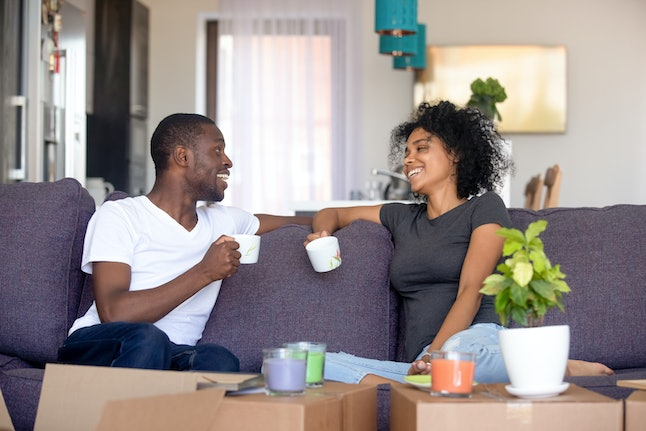 Happy afro couple rest on sofa in living room talking planning future life holds cups drinking tea, heap carton boxes with stuff. Moving day new home, preparations for relocation or renovation concept