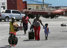 Evacuees carry their belongings as they walk to a ferry to depart for Nassau in the aftermath of Hur...