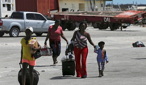 Evacuees carry their belongings as they walk to a ferry to depart for Nassau in the aftermath of Hurricane Dorian, at the port of Marsh Harbor, Abaco Island, Bahamas, . It's been nearly a week after disaster roared in from the sea as the most powerful hurricane in the northwestern Bahamas' recorded history