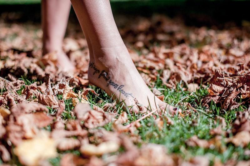 Beautiful feminine feet with tattoo.