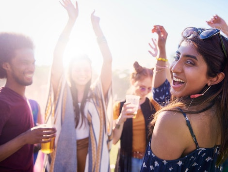 Happy Asian woman and her friends at the music festival