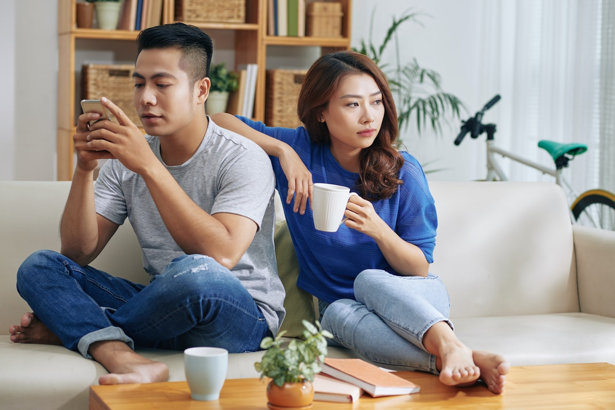 Asian couple sitting on couch and man surfing smartphone while woman looking bored and?lonely
