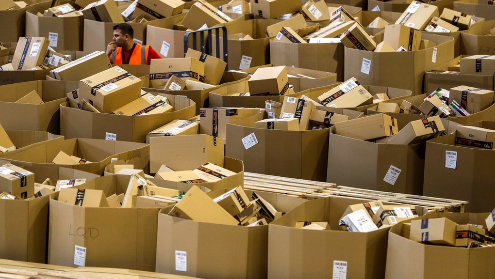 A worker stands between boxes at an Amazon distribution center during 'Black Friday' in Madrid, Spain, 24 November 2017. Black Friday is a huge shopping event which sees people all over the world getting discounted products as retailers slash prices. This year shoppers choose to shop online rather than traditionally queuing up through the night outside the shops before opening hours.