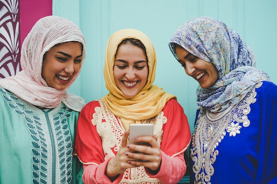 Happy Muslim women watching on mobile smart phone in the college - Arabian young girls having fun with new technologies trends apps - Millennials, Religion, culture and technology concept