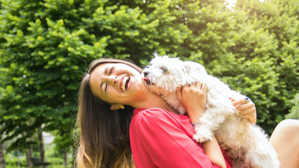 Caucasian woman laughing and having fun at the park with her puppy dog