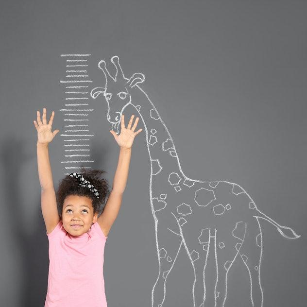 African-American child measuring height near chalk giraffe drawing on grey wall