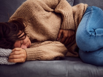 Woman having stomach issues / problems while lying on the couch.