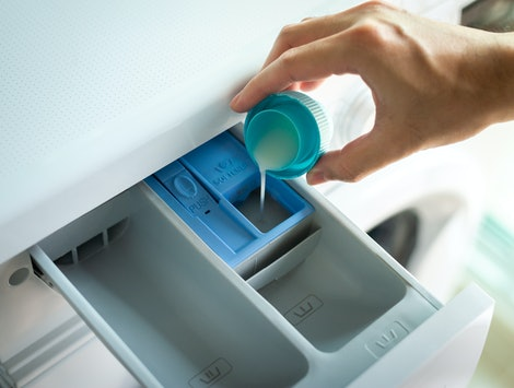 Man's hand pouring fabric softener into the washing machine detergent drawer.