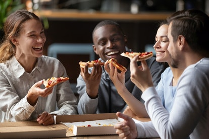 Cheerful multiracial happy best friends couples laugh at funny joke eating pizza in cafe together, happy multicultural young mates having fun sharing food at party meeting in pizzeria sit at table