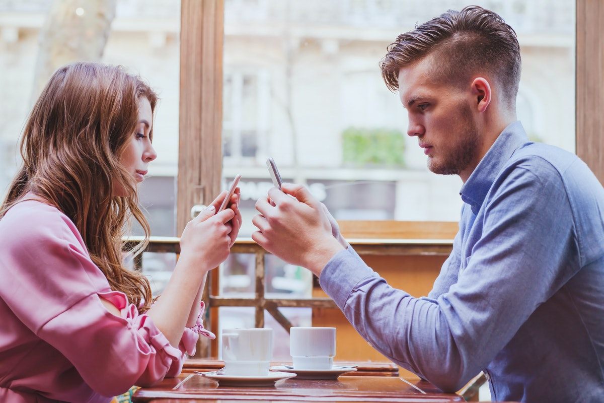 phubbing, always connected, internet addiction, young couple in cafe looking at their smartphones, s...