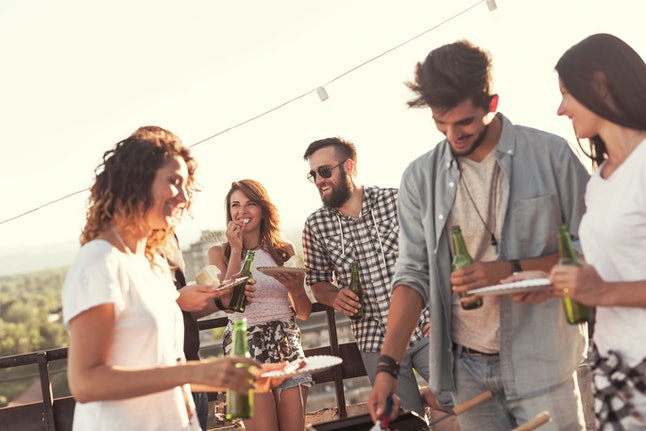 Group of young friends having fun at rooftop party, making barbecue and enjoying hot summer days. Focus on the couple in the background