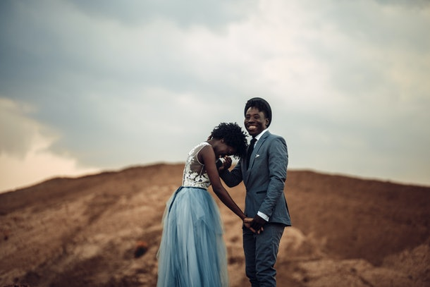 Black happy newlyweds hold hands, cheerful laugh and stand against beautiful landscape.