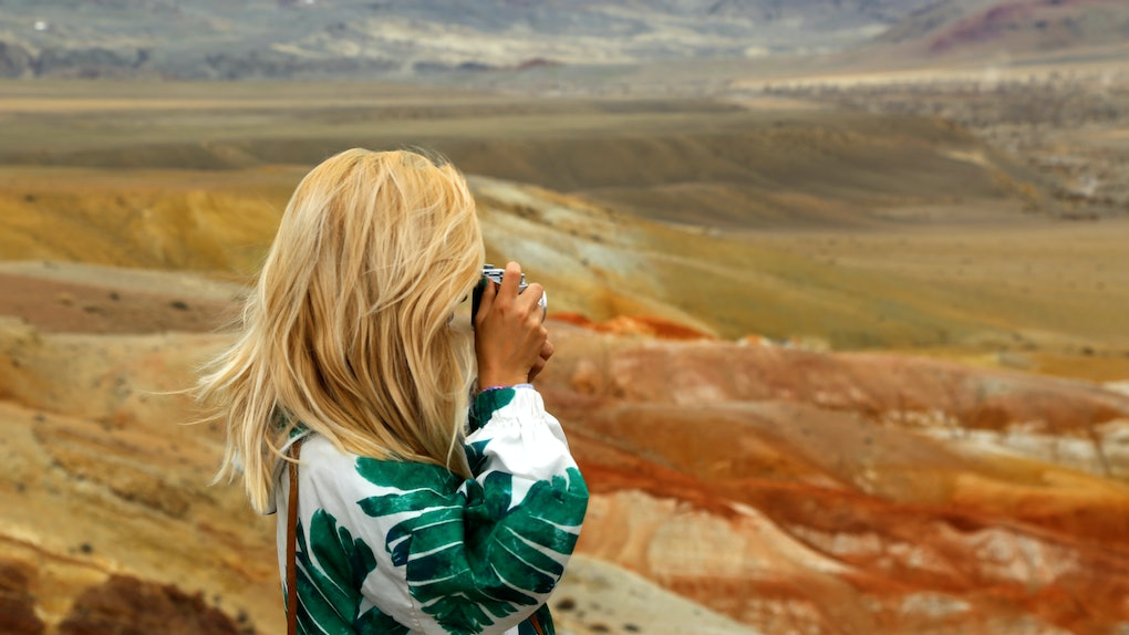 Blond woman traveller taking photo of red mountains in Altai in Russia. Valley of Mars landscapes in the Altai Mountains, Kyzyl Chin, Siberia, Russia