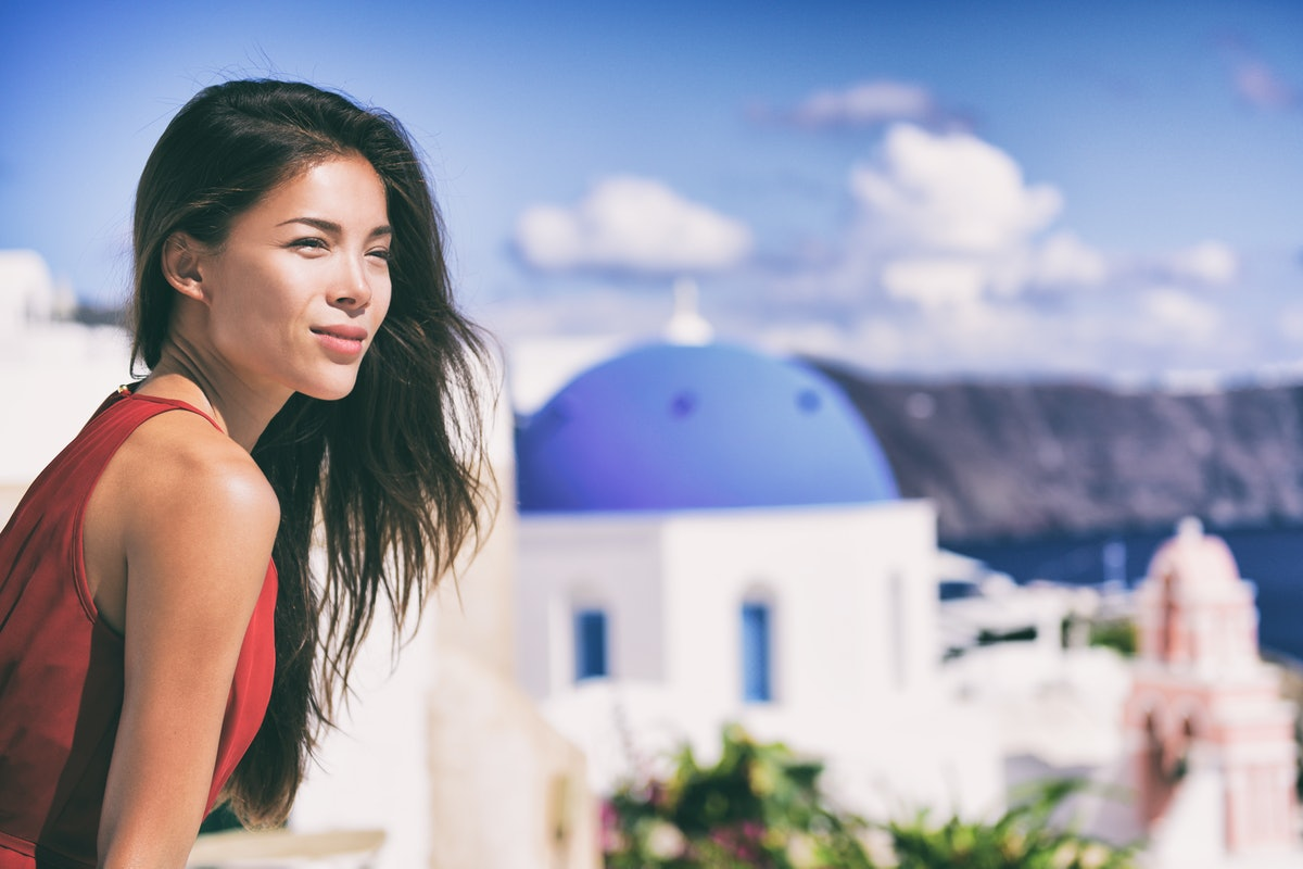 Luxury Europe cruise travel vacation Santorini woman looking at view. Tourist Asian girl relaxing at...