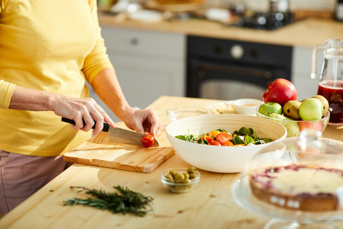 Close-up of unrecognizable woman in yellow sweater standing at kitchen counter and cutting tomato wh...