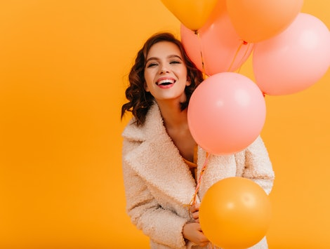 Attractive young woman holding pink balloons and smiling. Studio shot of blissful birthday girl isolated on yellow background.