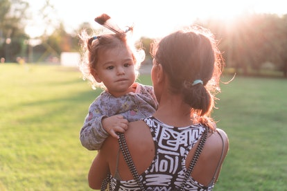 Young mother carrying kid in arms. Mom holding child outdoors in urban park in golden hour. Woman hugging toddler with feather in hair walking away from camera in nature at sunset.