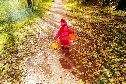 little girl in halloween costume trick or treating in autumn